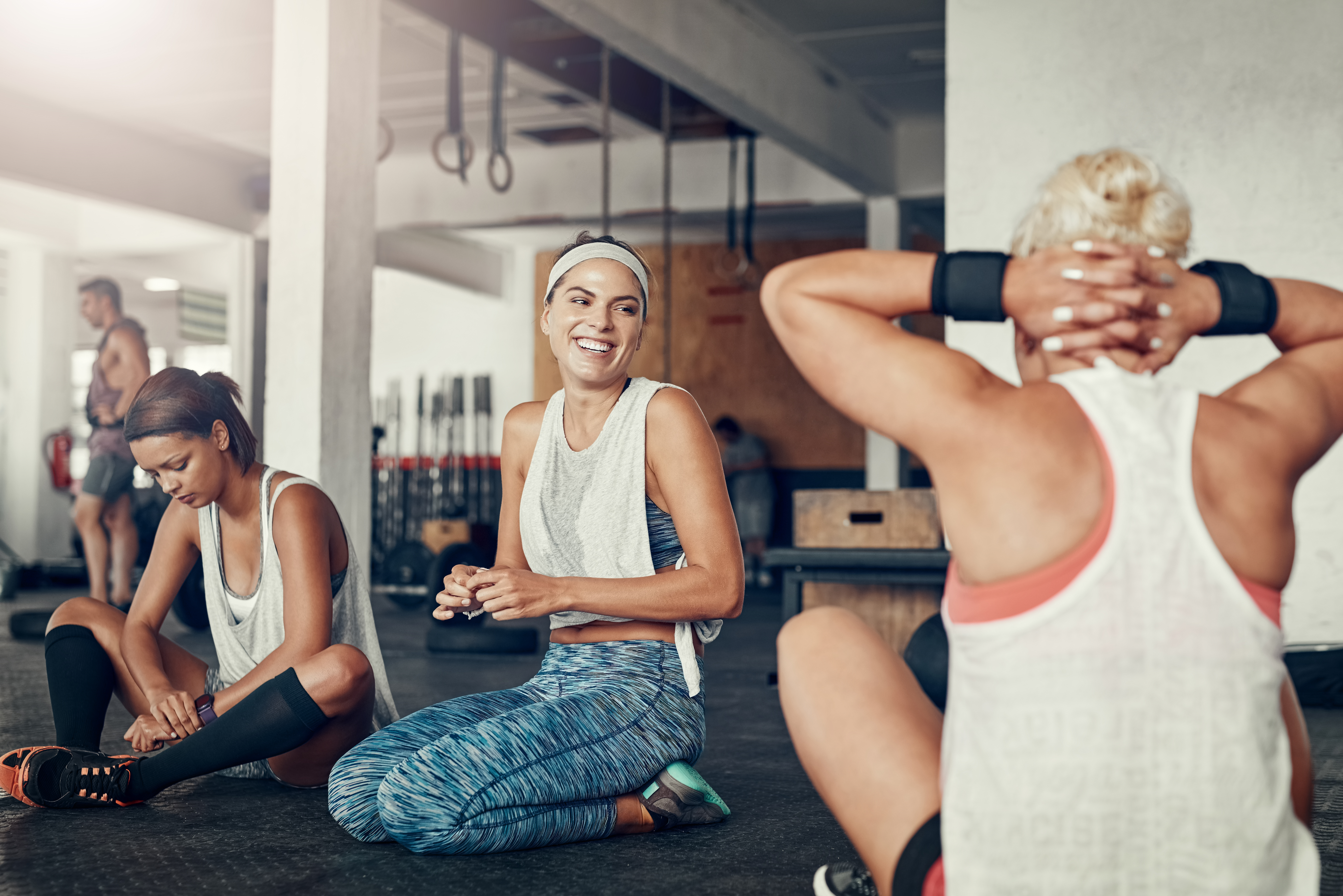 Shot of a group of young women taking a break together after a workout at the gym